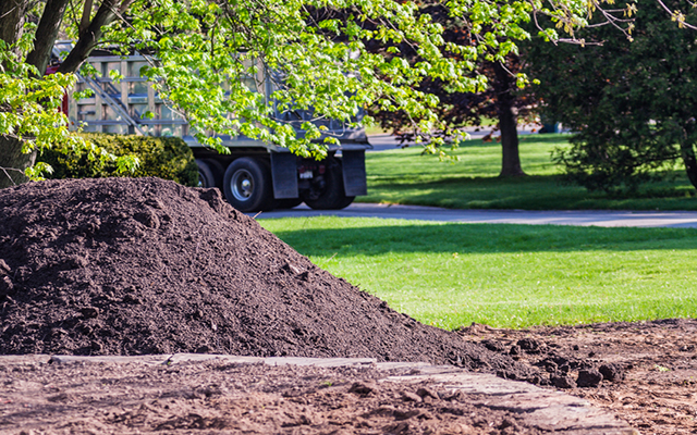 A heavy commercial dump truck has left a residential property after delivering a large pile of landscaping topsoil.